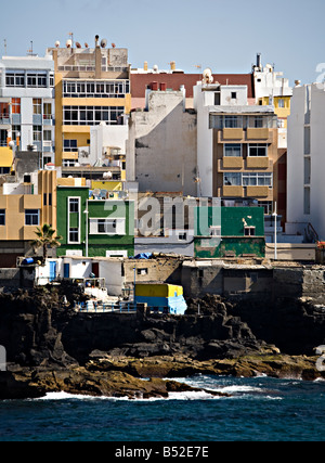 Run down and poorly maintained housing and buildings on rocky volcanic coast Las Palmas Gran Canaria Spain - Stock Photo