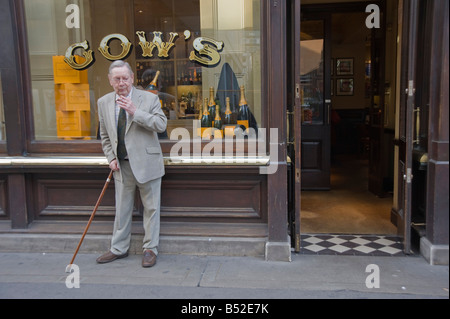 Man standing, smoking  outside Gow's champagne, Oyster bar and restaurant Old Broad street in the city of London - Stock Photo