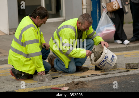 Two local authority workers repairing pavement wearing bright yellow high visibility jackets kneeling down, UK - Stock Photo
