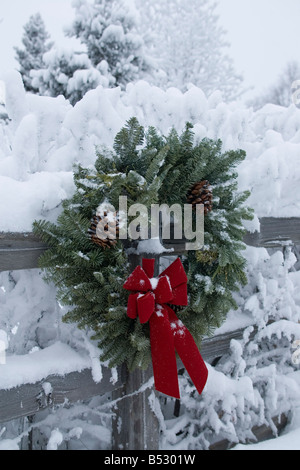 Holiday christmas wreath hanging on snow covered split rail fence Anchorage Alaska Southcentral Winter - Stock Photo