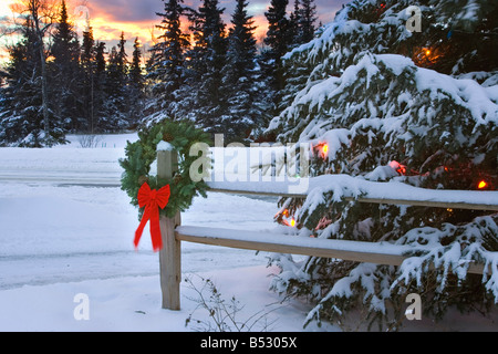 Holiday Wreath hanging on split-rail fence next to decorated tree w/sunset Anchorage Alaska Winter - Stock Photo