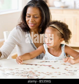 African grandmother helping granddaughter put together a puzzle - Stock Photo