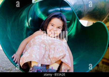 Mixed race girl sliding in playground