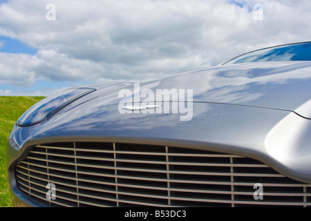Bonnet and Grille of a silver Aston Martin Vanquish with blue, cloudy sky behind - Stock Photo