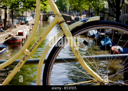 A bicycle framing a view of a canal in Amsterdam - Stock Photo