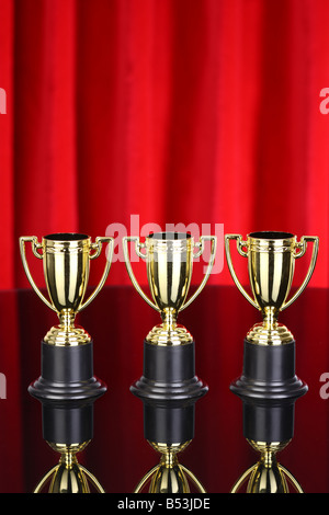Three trophies with red curtain background - Stock Photo