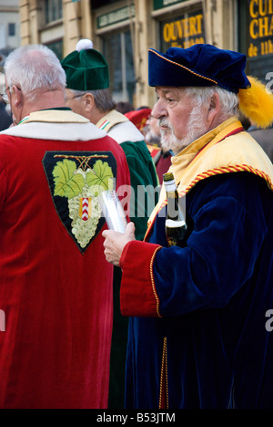 A member of the wine producer's association holding a stack of glasses and a bottle of wine of the Fete des Vendanges, - Stock Photo