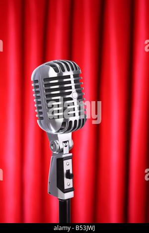 Classic retro microphone with red curtain background - Stock Photo