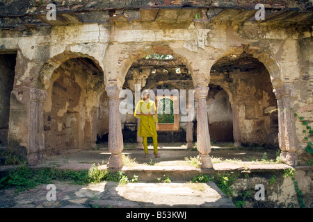 A young indian girl in traditional yellow costume stands between the arches in The Fort, Ranthambore National Park, - Stock Photo