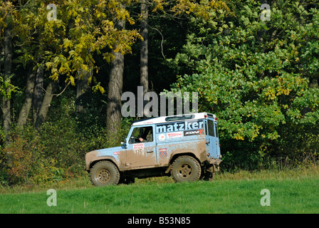 Muddy light blue Land Rover Defender 90 driving along a forest track in the Weserbergland. - Stock Photo