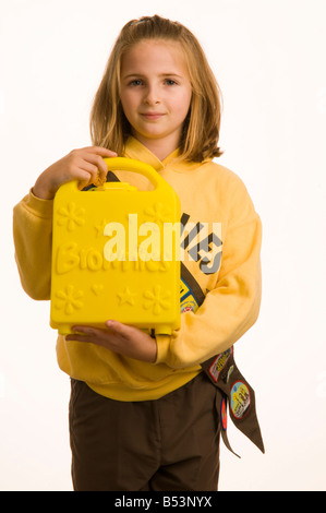10 year old girl dressed in her Brownies uniform holding her Brownie box - Stock Photo