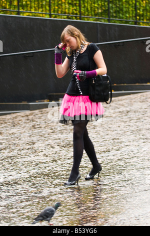 Rainy day in London , pretty young girl walks in rain on mobile phone dressed in Goth outfit with pink tutu skirt - Stock Photo