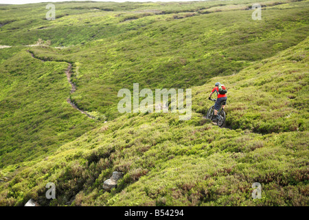 Mountain Biker Rides Alone on the North Yorkshire Moors - Stock Photo