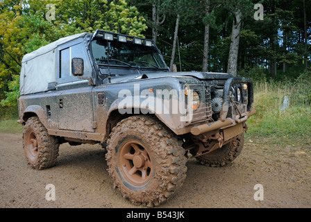 Muddy Land Rover Defender 90 on a forest track in the Weserbergland. - Stock Photo