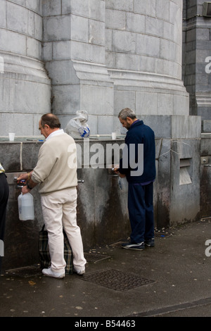 Filling holy water bottles - Lourdes, Southern France - Stock Photo