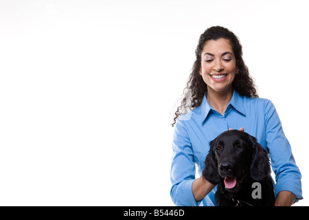 woman plays with one black dog on white background - Stock Photo