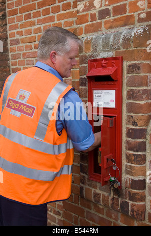 postman working for Royal Mail collecting mail from a postbox - Stock Photo