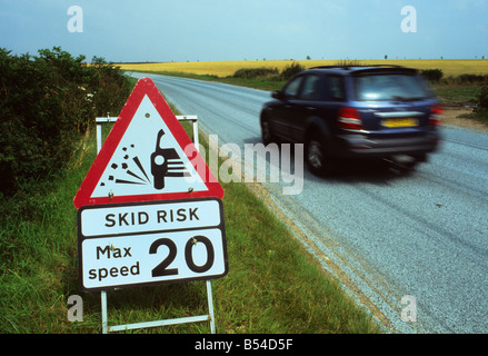 four by four vehicle passing warning sign of slippery road surface on newly resurfaced road near Leeds Yorkshire - Stock Photo