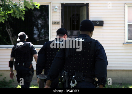Police officers from the Detroit Narcs approach a house suspected of dealing drugs - Stock Photo