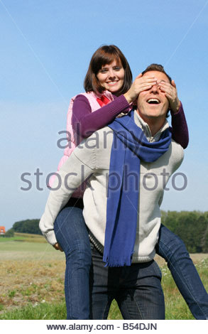 young couple playing in autumn landscape - Stock Photo