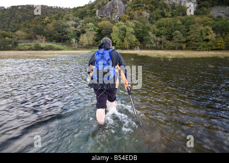 A walker makes his way through flooded terrain on the edge of Derwent Water in the Lake District Cumbria England - Stock Photo