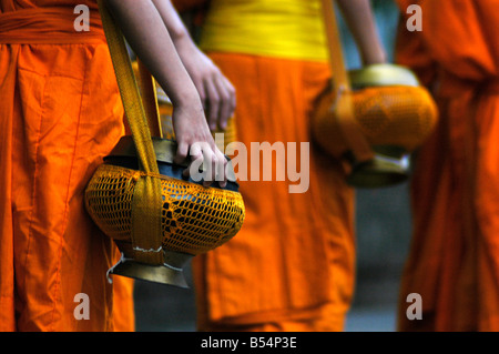 Monks make their daily rounds to receive alms from Buddhist followers In LuangPrabang - Stock Photo