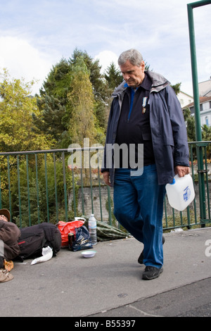 Man on the way to fill holy water, but ignoring the homeless man on the way - Lourdes, Southern France - Stock Photo