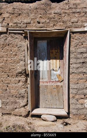 Old wooden door in adobe building in New Mexico - Stock Photo