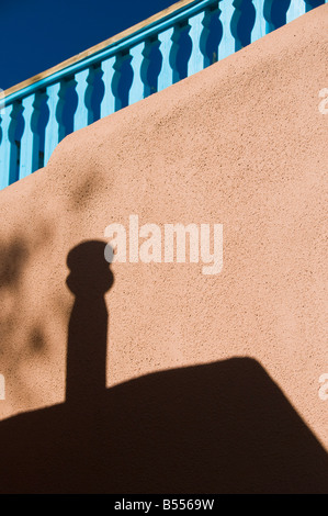 Graphic fence building and shadow on adobe wall in Taos NM - Stock Photo