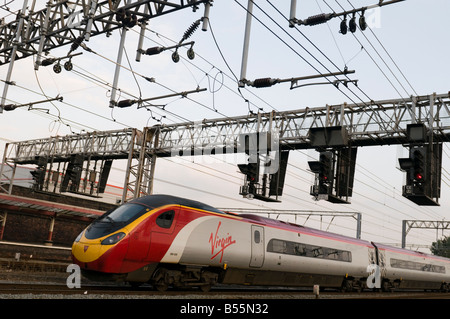 A Virgin Trains pendolino inter-city train arriving  at running on the West Coast main line arriving AT Crewe Railway - Stock Photo