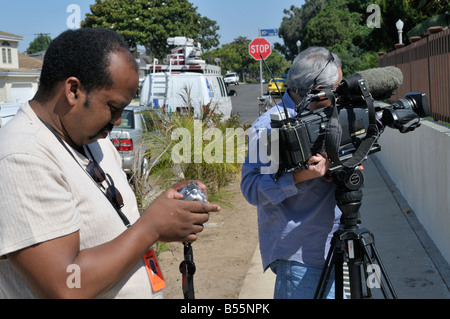 Local print media photographer checking his picts on his digital camera - Stock Photo