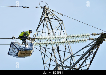 London team of electrical engineers working on high voltage powerline pylons - Stock Photo