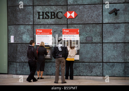 People queueing at HSBC cashpoint - Stock Photo