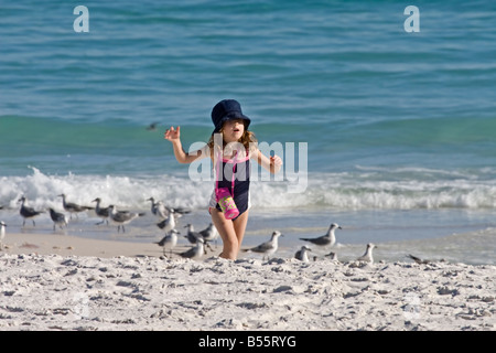 Little girl in sun hat running and playing on the white sand beach while on vacation in Florida. - Stock Photo