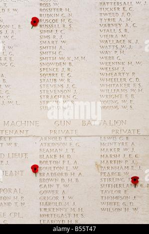 Red poppies on list of war dead from machine gun battalion Tyne Cot British War Memorial cemetery Belgium - Stock Photo
