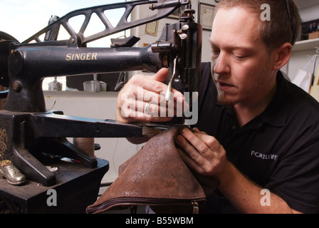 A man uses an antique Singer sewing machine to repair leather goods in a small shop in Maryland USA - Stock Photo