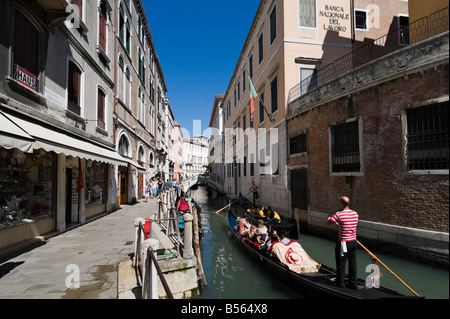 Tourists on Gondolas on a narrow canal in the district of San Marco, Venice, Veneto, Italy - Stock Photo