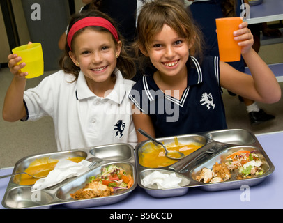 SCHOOL DINNERS Junior school girls pupils 7-9 years holding water beakers toasting a healthy balanced prepared lunch - Stock Photo