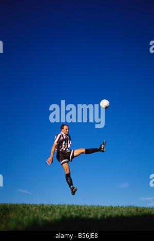 Male soccer player kicks the ball - Stock Photo