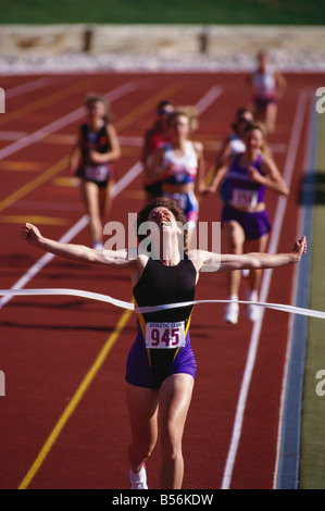 Women victoriously crossing the finish line of track race - Stock Photo