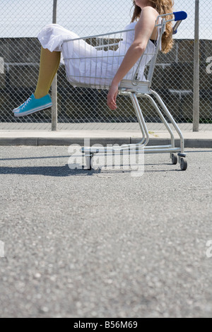 Woman sitting in a shopping trolley - Stock Photo