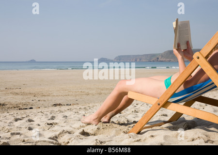 Woman reading a book on an empty beach - Stock Photo