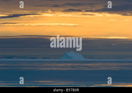Frozen in iceberg is surrounded by spring melt water at Lancaster Sound Nunavut Canada Arctic - Stock Photo