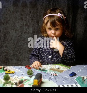 Crafts Child playing on applique map play mat - Stock Photo