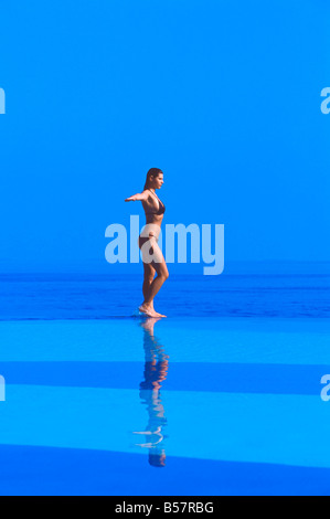 Woman walking at the Edge of Infinity pool, Maldives, Indian Ocean, Asia - Stock Photo