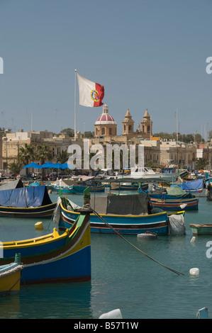 Brightly coloured fishing boats called Luzzus at the fishing village of Marsaxlokk, Malta, Mediterranean, Europe - Stock Photo