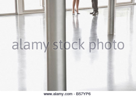 Co-workers talking in office lobby - Stock Photo