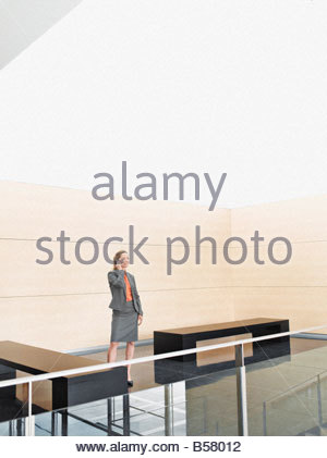 Businesswoman talking on cell phone in lobby - Stock Photo