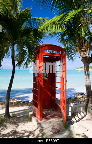 Traditional English red telephone box on the beach at Dickenson Bay, Antigua, Leeward Islands, West Indies, Caribbean - Stock Photo