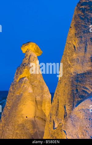 Fairy chimneys known as The Three Beauties illuminated at night near Goreme, Cappadocia, Central Anatolia, Turkey - Stock Photo